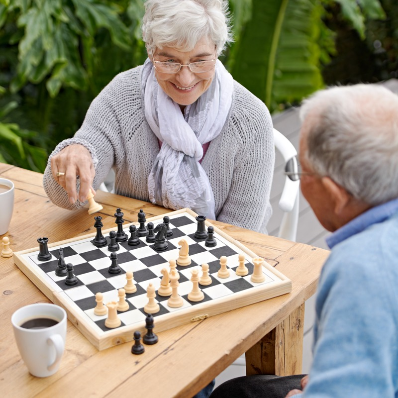 Senior woman and man playing chess in the outdoor courtyard