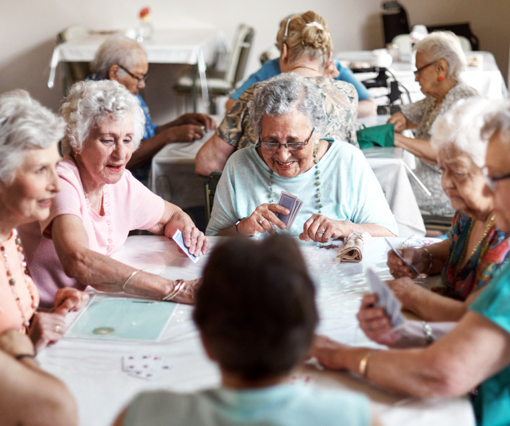 group of senior women playing cards in the community room